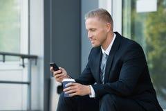 Hombre de negocios que mira el teléfono celular foto de archivo