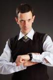Hombre de negocios que mira en su reloj Imagen de archivo libre de regalías