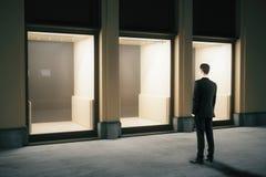 Hombre de negocios que mira exterior de la tienda Imagen de archivo