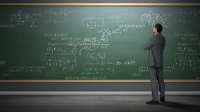 Hombre de negocios que mira fórmulas almacen de video