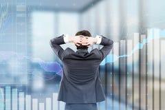 Hombre de negocios que mira gráficos en oficina Imagen de archivo libre de regalías