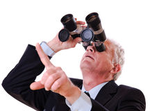 Hombre de negocios que mira hacia arriba a través de los prismáticos Foto de archivo libre de regalías