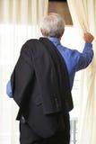 Hombre de negocios que mira hacia fuera la ventana Imagenes de archivo