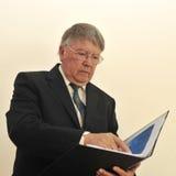 Hombre de negocios que mira la carpeta abierta Fotografía de archivo libre de regalías