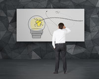 Hombre de negocios que mira a la lámpara en el cartel Imágenes de archivo libres de regalías