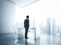 Hombre de negocios que mira la megalópoli a través de ventana foto de archivo