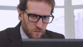 Hombre de negocios que mira la pantalla del ordenador portátil metrajes