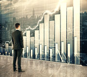 Hombre de negocios que mira la pantalla grande con el gráfico de negocio imágenes de archivo libres de regalías