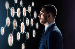 Hombre de negocios que mira la red de los contactos foto de archivo