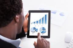 Hombre de negocios que mira la tableta digital Foto de archivo libre de regalías