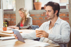 Hombre de negocios que mira la tableta digital en oficina Imagen de archivo libre de regalías