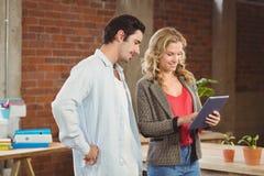 Hombre de negocios que mira la tableta digital y a la mujer que gesticulan en oficina Fotos de archivo libres de regalías