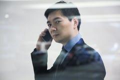 Hombre de negocios que mira la ventana completa en el parking, reflexión del coche Imágenes de archivo libres de regalías