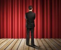 Hombre de negocios que mira a las cortinas rojas Imagen de archivo