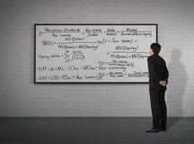 Hombre de negocios que mira a las fórmulas matemáticas Foto de archivo