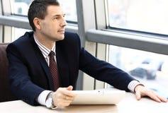 Hombre de negocios que mira lejos en ventana Fotos de archivo