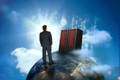 Hombre de negocios que mira los servidores encima del mundo Fotografía de archivo libre de regalías