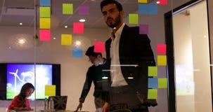 Hombre de negocios que mira notas pegajosas en la oficina 4k almacen de video