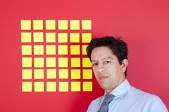 Hombre de negocios que mira para amarillear los papeles Foto de archivo libre de regalías