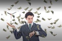 Hombre de negocios que mira su reloj con lluvia del dinero alrededor de él Imagen de archivo