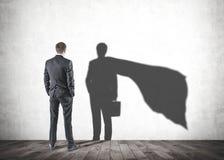 Hombre de negocios que mira su sombra del superhombre foto de archivo