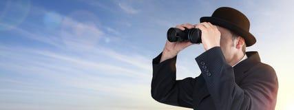 Hombre de negocios que mira a través de los prismáticos Imágenes de archivo libres de regalías