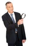 Hombre de negocios que mira a través de una lupa Imagen de archivo libre de regalías