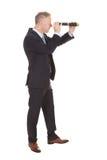 Hombre de negocios que mira a través del telescopio del PDA Imagenes de archivo