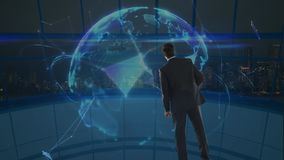 Hombre de negocios que mira un globo de giro de la tierra rodeado por las conexiones de datos