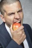 Hombre de negocios que muerde la manzana imagen de archivo libre de regalías