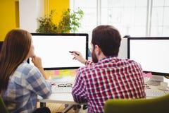 Hombre de negocios que muestra algo al compañero de trabajo femenino en el ordenador Foto de archivo