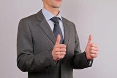 Hombre de negocios que muestra dos pulgares encima del cierre de la muestra para arriba Trabajo en equipo, concepto del éxito Foto de archivo