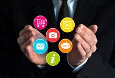 Hombre de negocios que muestra iconos virtuales coloridos Imagen de archivo libre de regalías