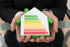 Hombre de negocios que muestra la carta económica de energía en modelo de la casa Fotografía de archivo
