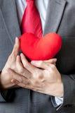 Hombre de negocios que muestra la compasión que lleva a cabo el corazón rojo sobre su pecho fotografía de archivo