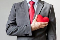 Hombre de negocios que muestra la compasión que lleva a cabo el corazón rojo sobre su pecho en su traje - crm, concepto del negoc foto de archivo