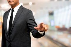 Hombre de negocios que muestra la mano y el finger con backgrou de la manera de pasillo de la falta de definición Fotos de archivo
