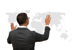 Hombre de negocios que muestra la mano y el finger con la carta del mapa del mundo Foto de archivo libre de regalías