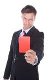 Hombre de negocios que muestra la tarjeta roja Imagen de archivo libre de regalías