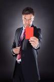 Hombre de negocios que muestra la tarjeta roja Fotografía de archivo libre de regalías