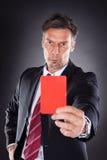 Hombre de negocios que muestra la tarjeta roja Imagen de archivo
