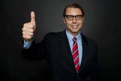Hombre de negocios que muestra los pulgares encima de la muestra a sus personas Fotos de archivo