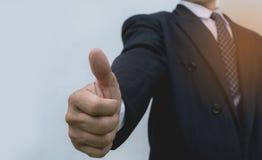 Hombre de negocios que muestra los pulgares para arriba que hacen el gesto ACEPTABLE Foto de archivo