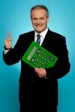 Hombre de negocios que muestra los pulgares para arriba, sosteniendo la calculadora Fotografía de archivo libre de regalías
