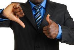 Hombre de negocios que muestra los pulgares para arriba y los pulgares abajo Fotos de archivo libres de regalías