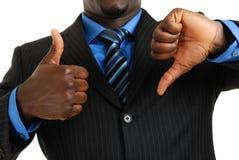 Hombre de negocios que muestra los pulgares para arriba y los pulgares abajo Foto de archivo libre de regalías