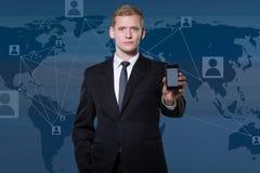 Hombre de negocios que muestra smartphone Imagen de archivo libre de regalías