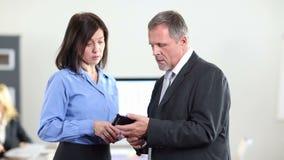 Hombre de negocios que muestra smartphone de la mujer en oficina