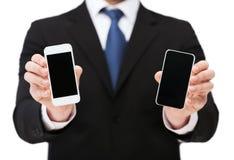 Hombre de negocios que muestra smartphones con las pantallas en blanco imagen de archivo libre de regalías