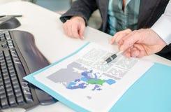 Hombre de negocios que muestra un documento económico con una pluma Foto de archivo libre de regalías